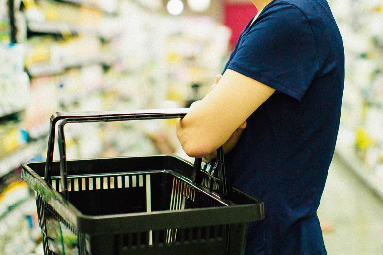 A person carries a basket on their arm in the middle of two stacked grocery aisles.
