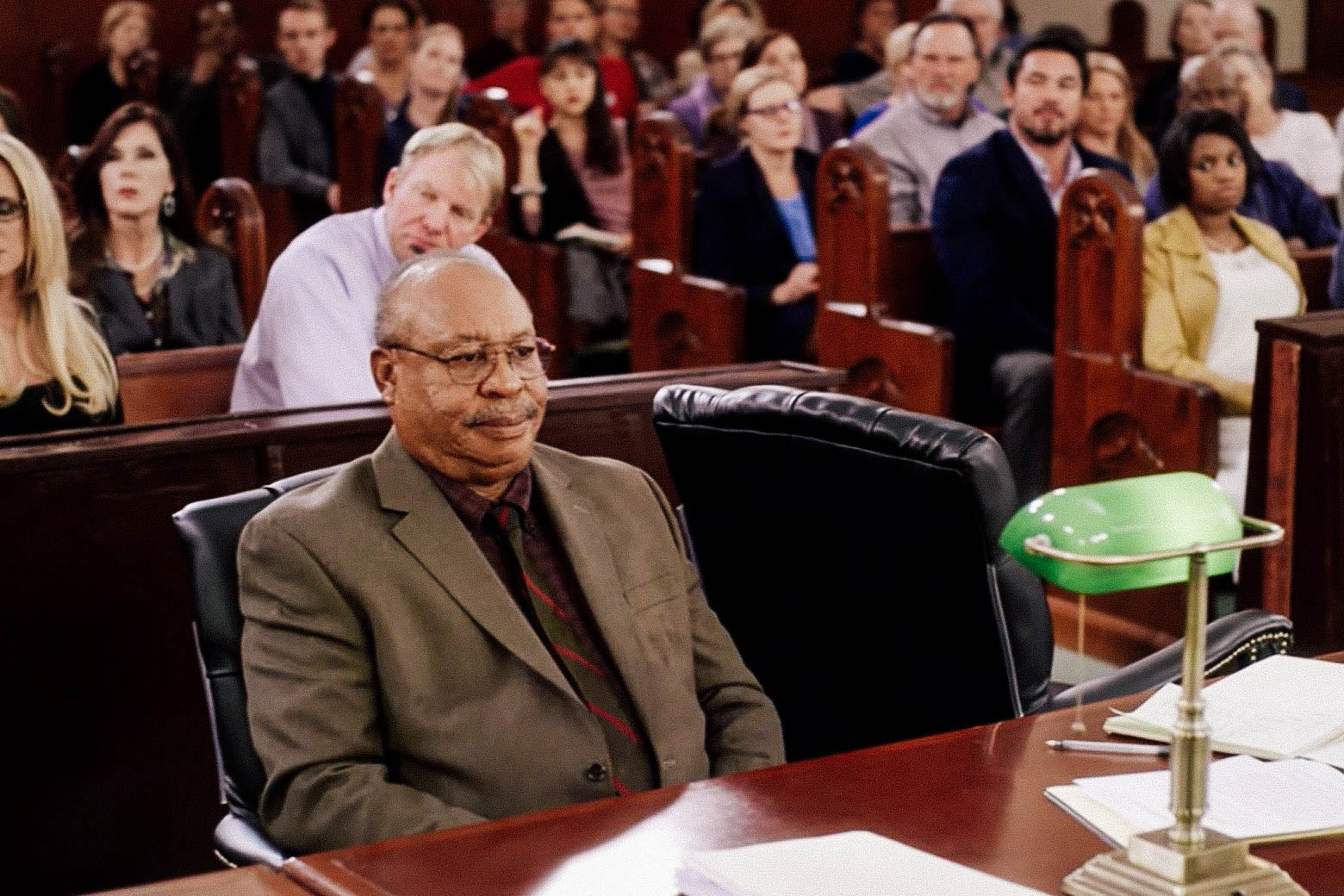 In this still from Gosnell, Earl Billings as Dr. Kermit Gosnell sits behind a table in a courtroom.