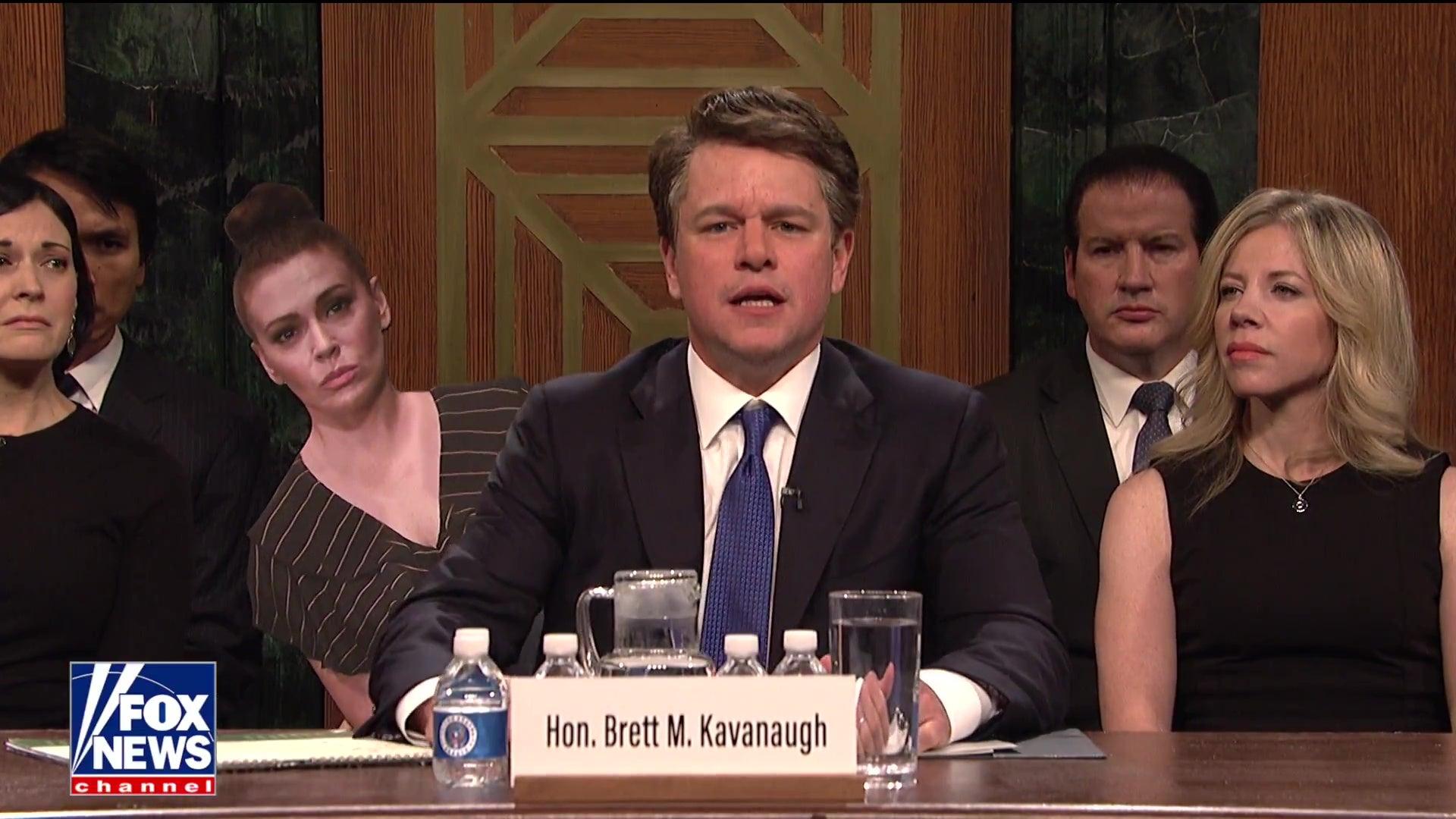Matt Damon, as Brett Kavanaugh, sits at the hearing table weeping.