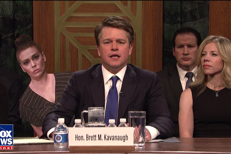 Matt Damon, as Brett Kavanaugh, sits at the hearing table weeping.