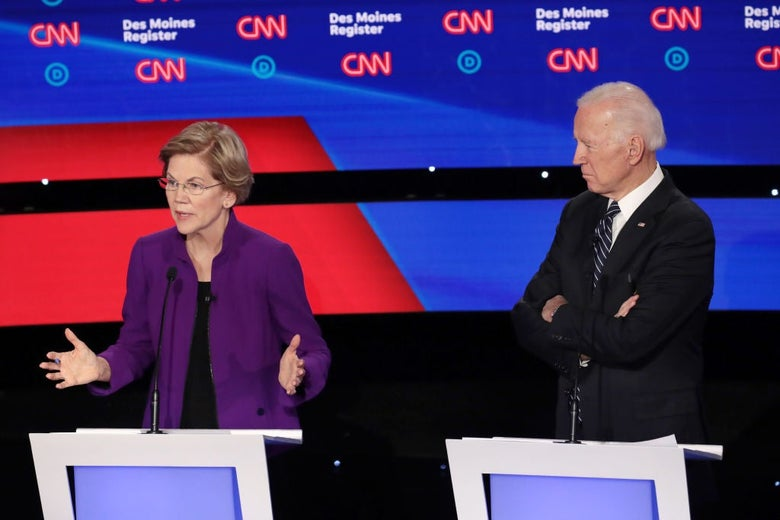 Warren gestures while speaking from her lectern as Biden watches with his arms folded, standing behind the lectern next to hers.