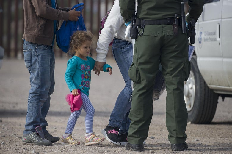 A young child is processed by Border Patrol agents.