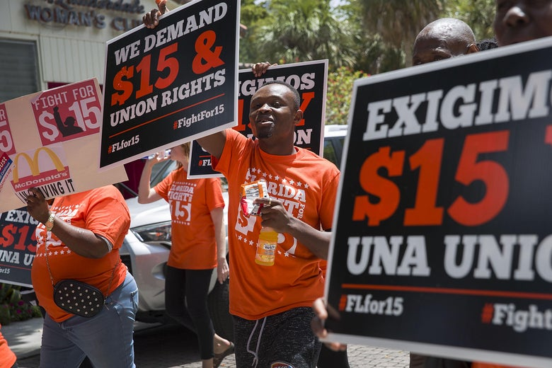 Activists march and carry signs demanding that McDonald's raise workers' wages to a $15 minimum on May 23, 2019, in Fort Lauderdale, Florida