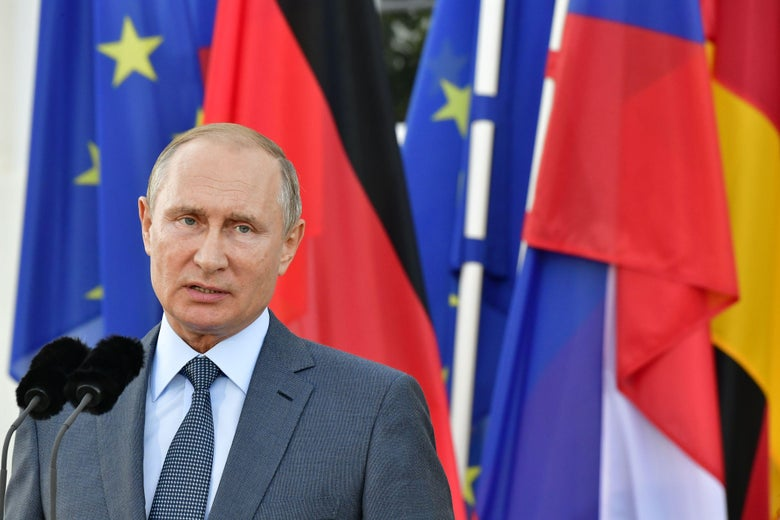 Russian President Vladimir Putin stands behind a microphone and in front of a backdrop of flags