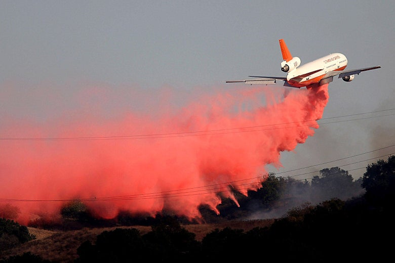 A plane leaves behind it a trail of red smoke.