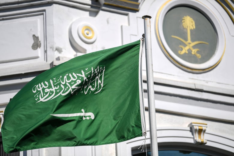 The flag of Saudi Arabia in front of an ornate building.