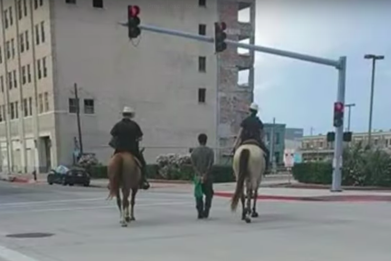 A bystander photo of the arrest shows Neely between two mounted officers.