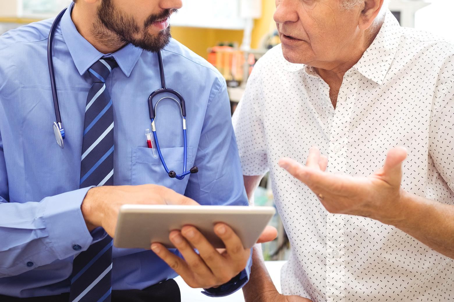 A stock photo depicts a doctor assessing a patient's needs.