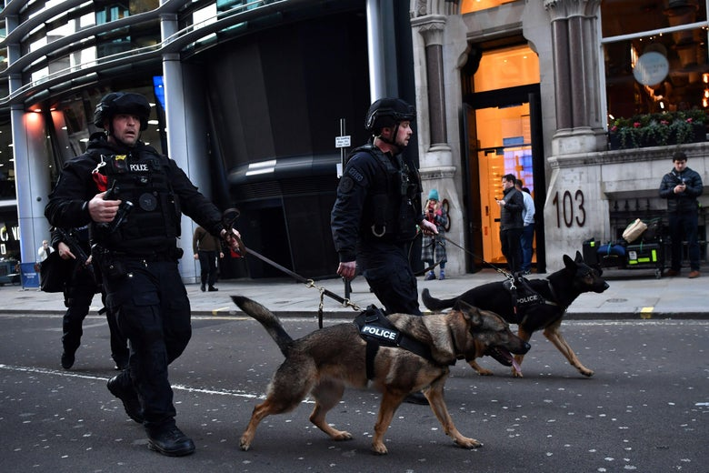 Armed police with dogs patrol along Cannon Street in central London on November 29, 2019 after reports of shots being fired on London Bridge.