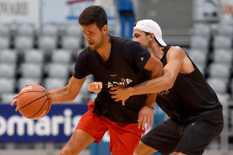 Dimitrov guards Djokovic, who is dribbling the basketball