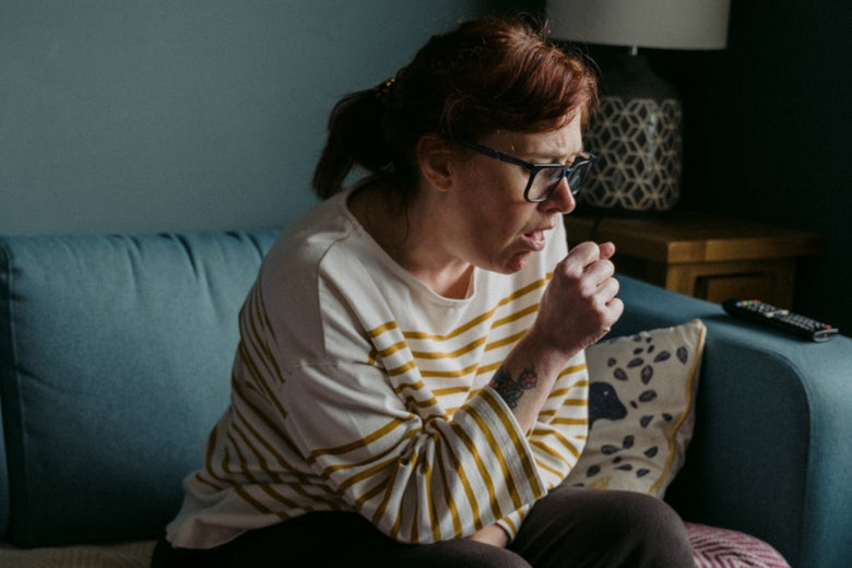A woman sitting on a couch coughs.