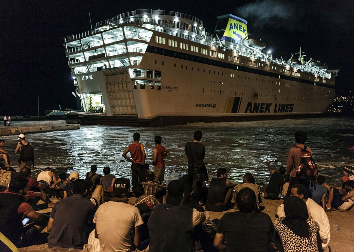 Syrian migrants wait on a dock to board on the Eleftherios Veniz
