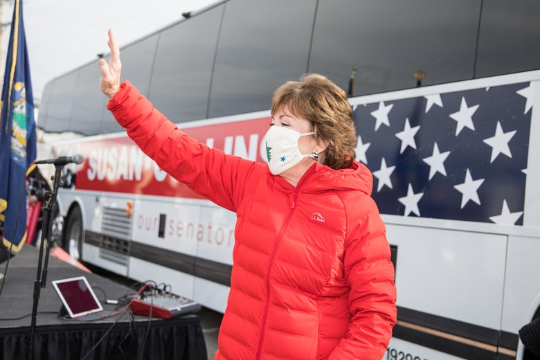 Susan Collins stands in front of her campaign bus, waving to supporters