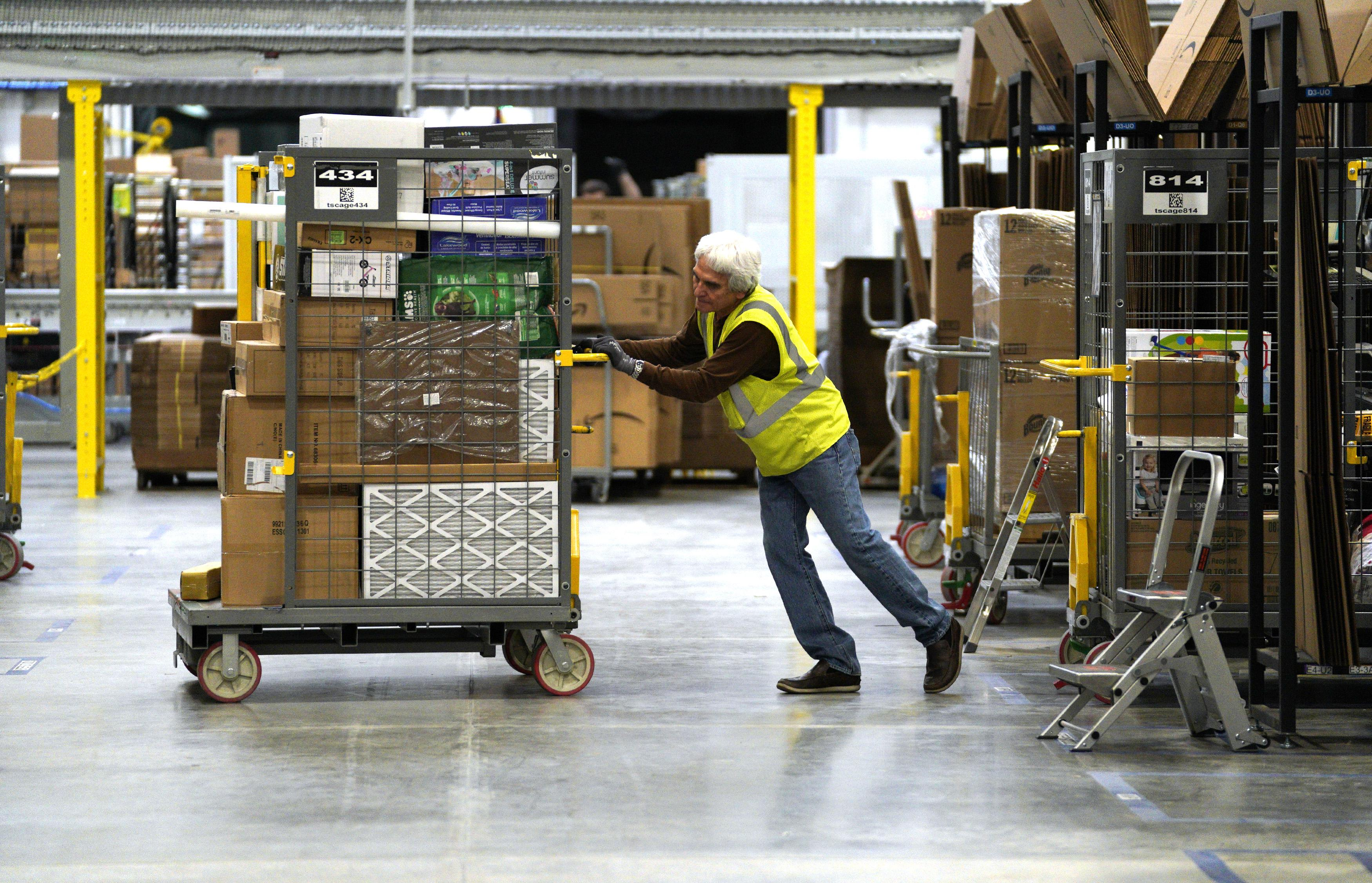A worker moves boxes at an Amazon fulfillment center.