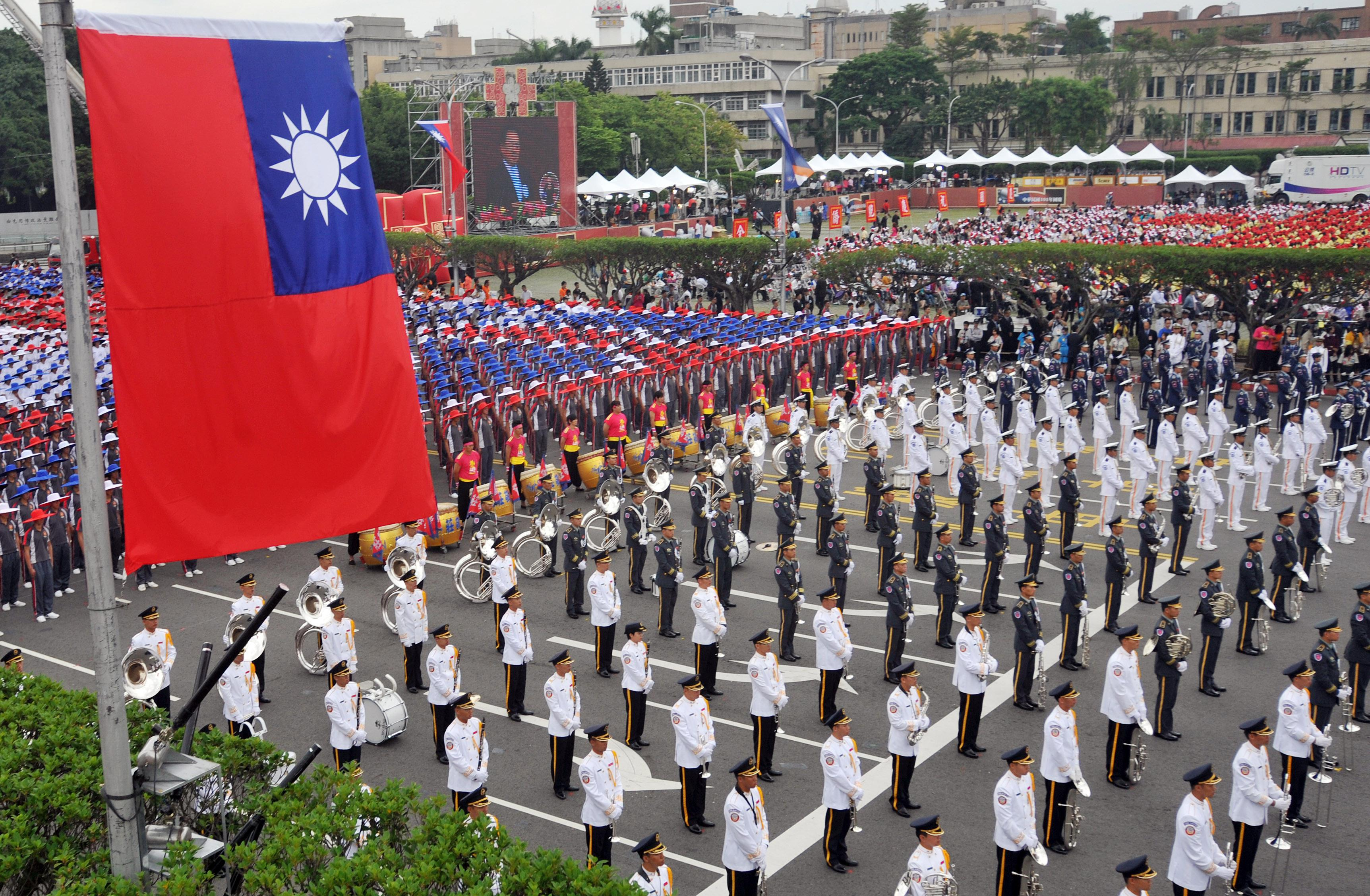 Members of a Taiwanese military band and people wearing hats in the colors of Taiwan's national flag.