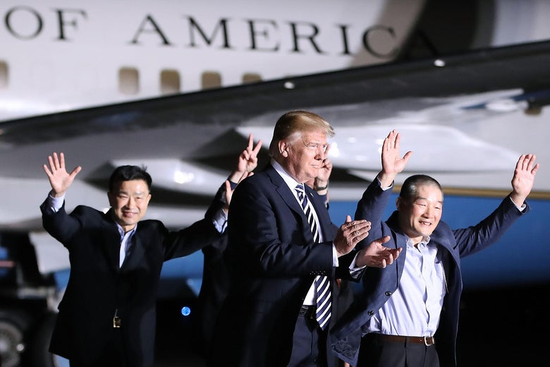 Trump walking beside Air Force One along with three dressed-up men waving.