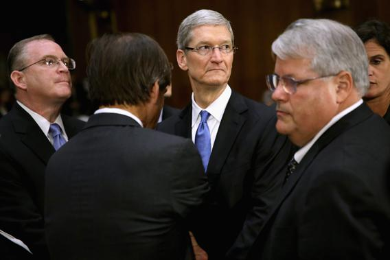 Apple head of tax operations Phillip Bullock (L), Apple CEO Timothy Cook (2nd R) and  Apple Senior Vice President and CFO Peter Oppenheimer (R) take a break from their testimony before the Senate Homeland Security and Governmental Affairs Committee's Investigations Subcommittee about the company's offshore profit shifting and tax avoidance in the Dirksen Senate Office Building on Capitol Hill May 21, 2013 in Washington, DC.
