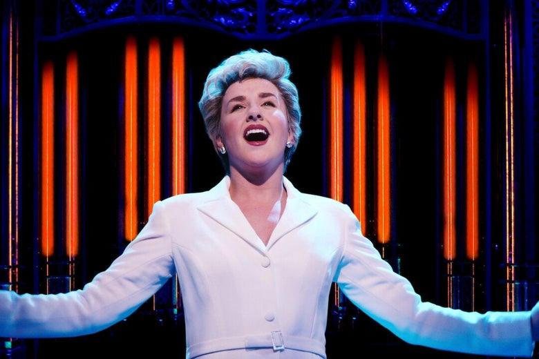 De Waal wearing a white collared dress and Diana's feathered shag haircut raises her arms at her sides as she sings onstage
