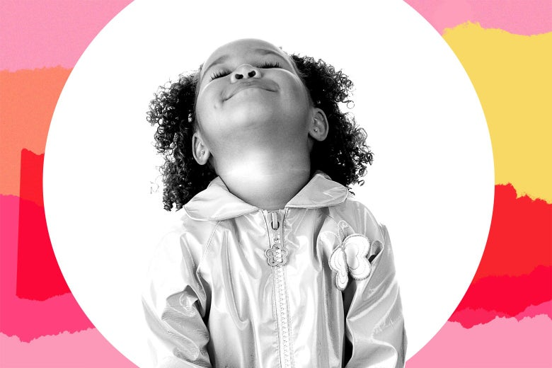 A young biracial girl in a raincoat looking up with her eyes closed.