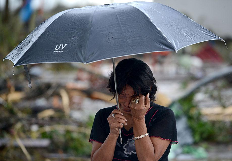 A woman mourns in front of her husband's dead body in a street of Tacloban, eastern island of Leyte on November 10, 2013.
