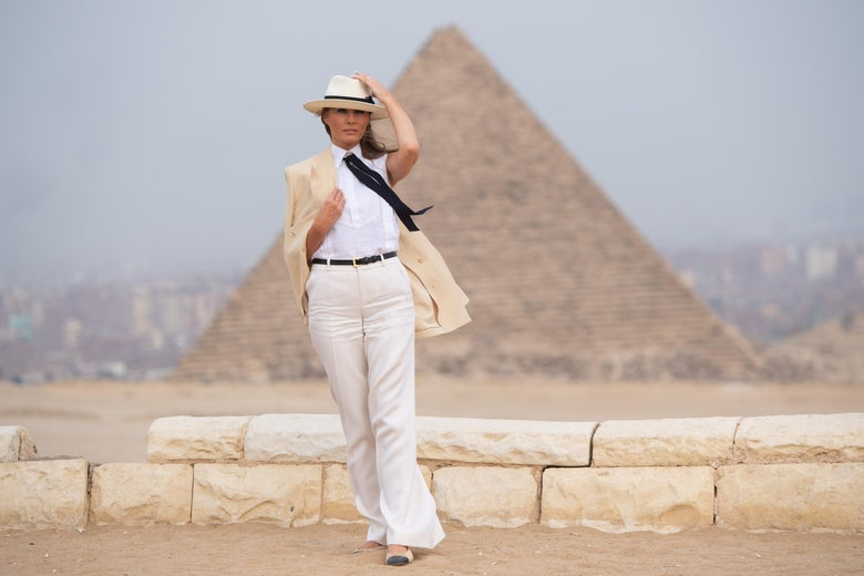 Melania Trump clasps her beige blazer with one hand and her cream fedora with the other in front of a gigantic pyramid. She wears a white shirt and long black tie.