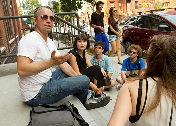 William Powhida sitting on the steps of the defunct Roebling Hall gallery in Williamsburg, Brooklyn, in August 2012.