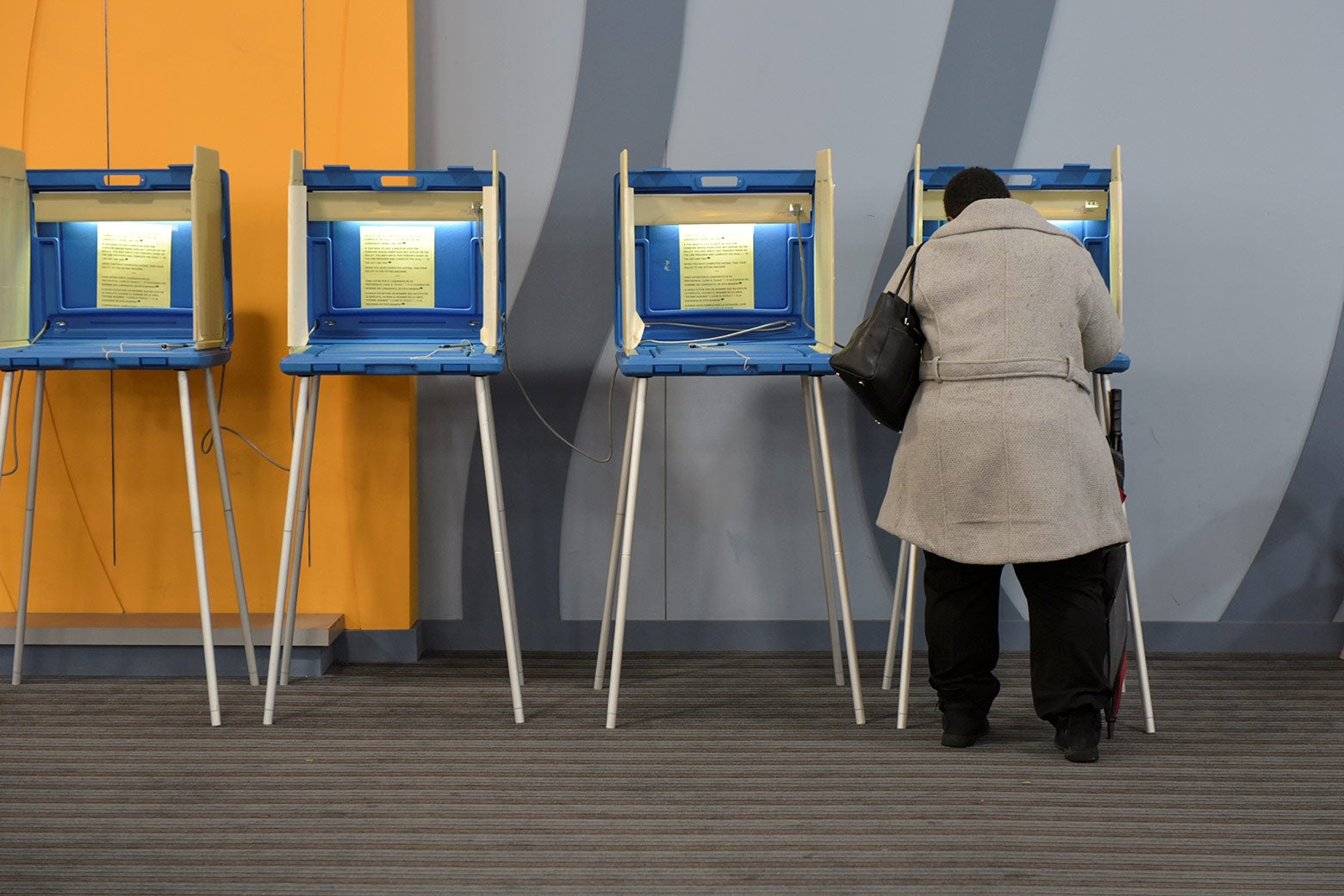 A woman using a voting machine.