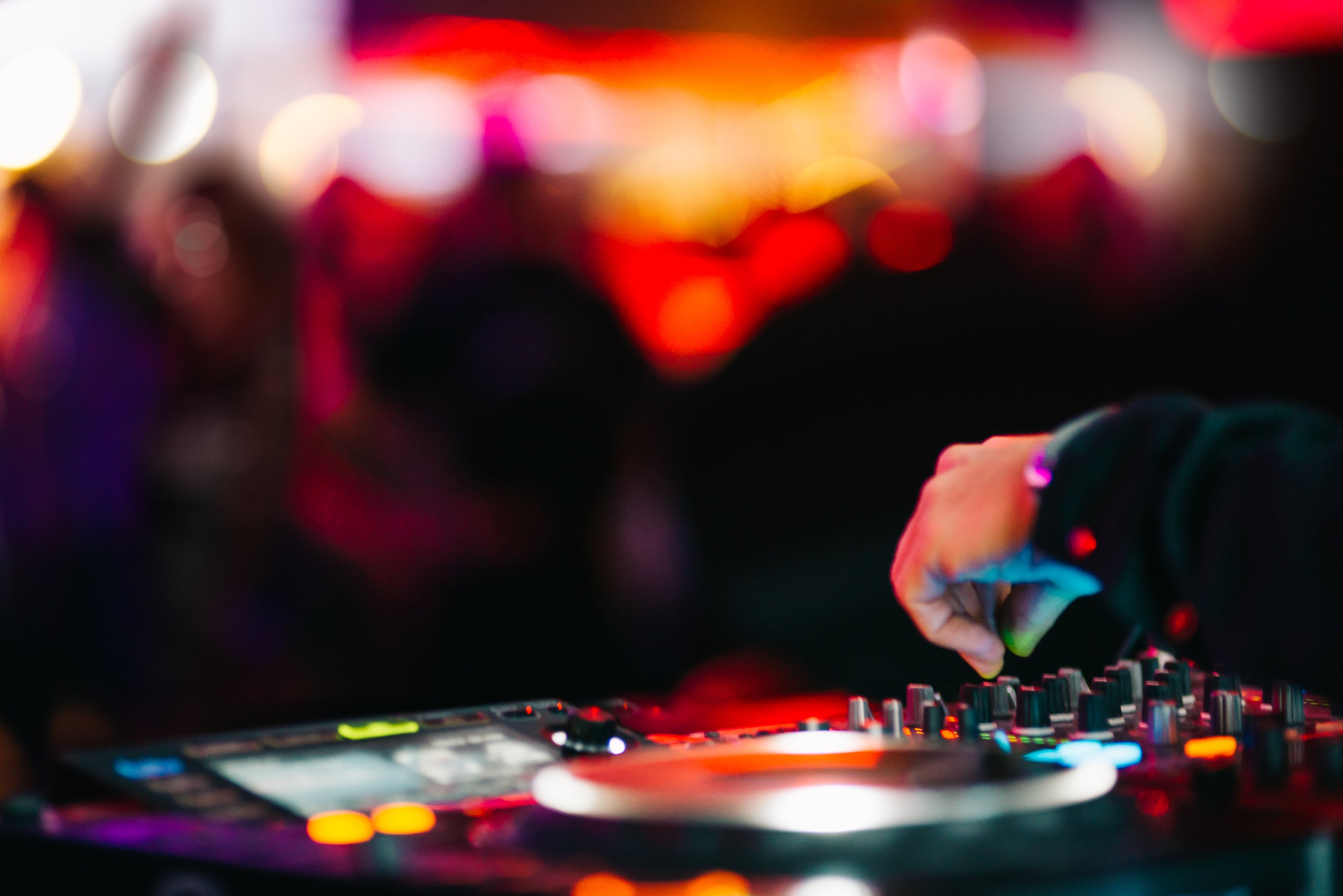 A DJ spinning in front of a dance club crowd.