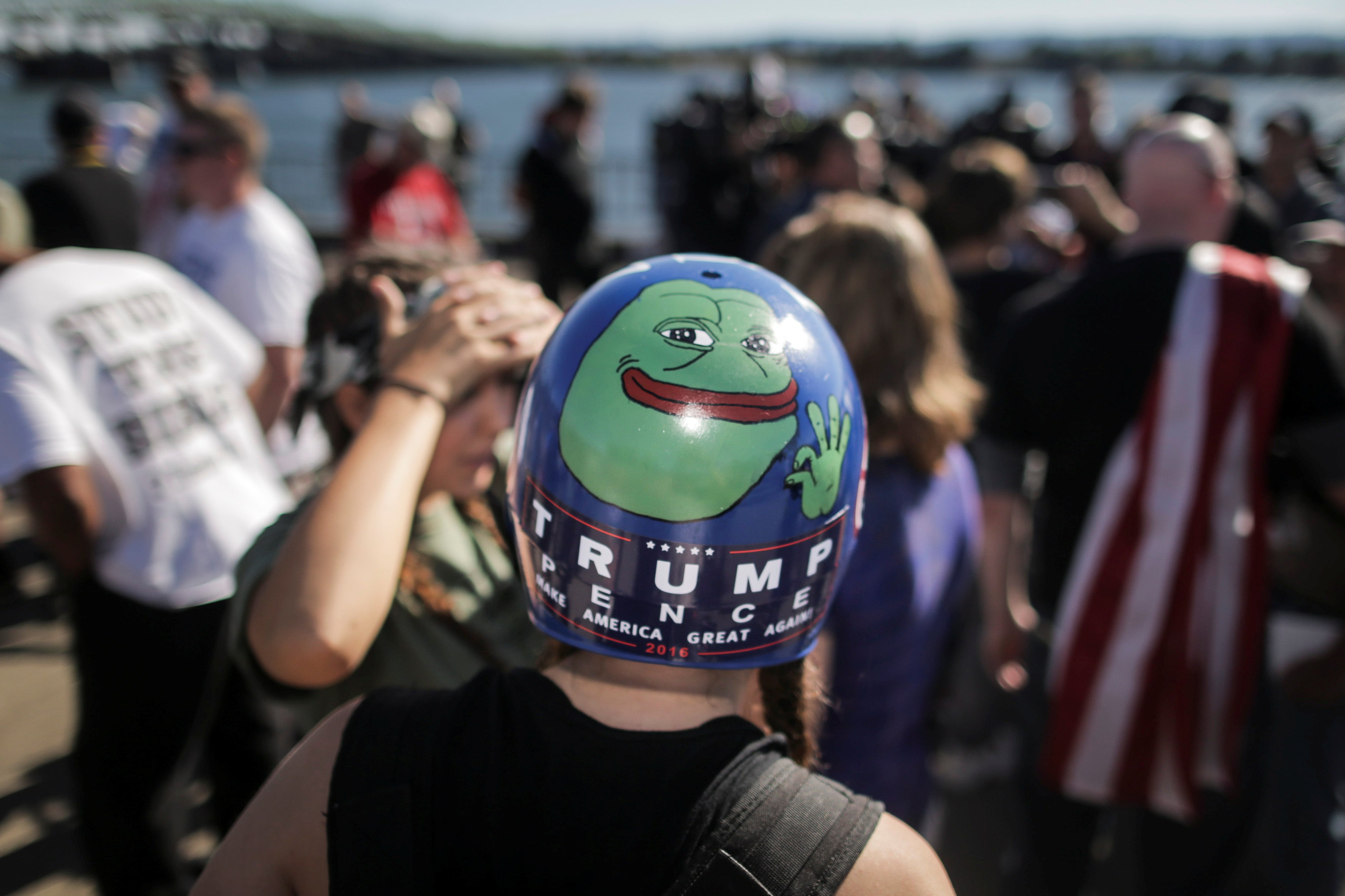 A Trump supporter wears a helmet with a hand-painted Pepe the Frog image.