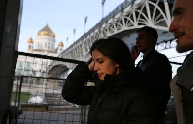 Nadezhda Tolokonnikova walks to her news conference at Dozhd TV channel with the Cathedral of Christ the Savour on the background, Dec. 27, 2014.