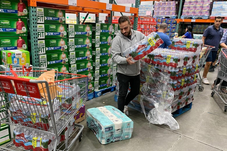 A man in a grocery store takes a case of water bottles from the top of a stack and looks at his shopping cart, which also has a case of water.