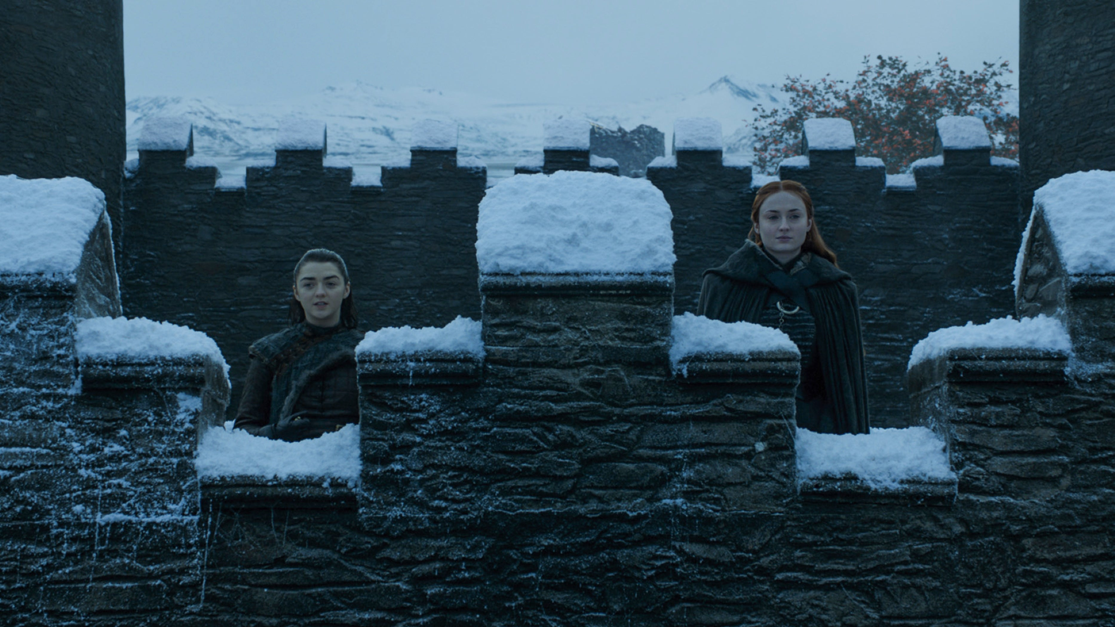 Maisie Williams and Sophie Turner stand behind a snow-covered wall.