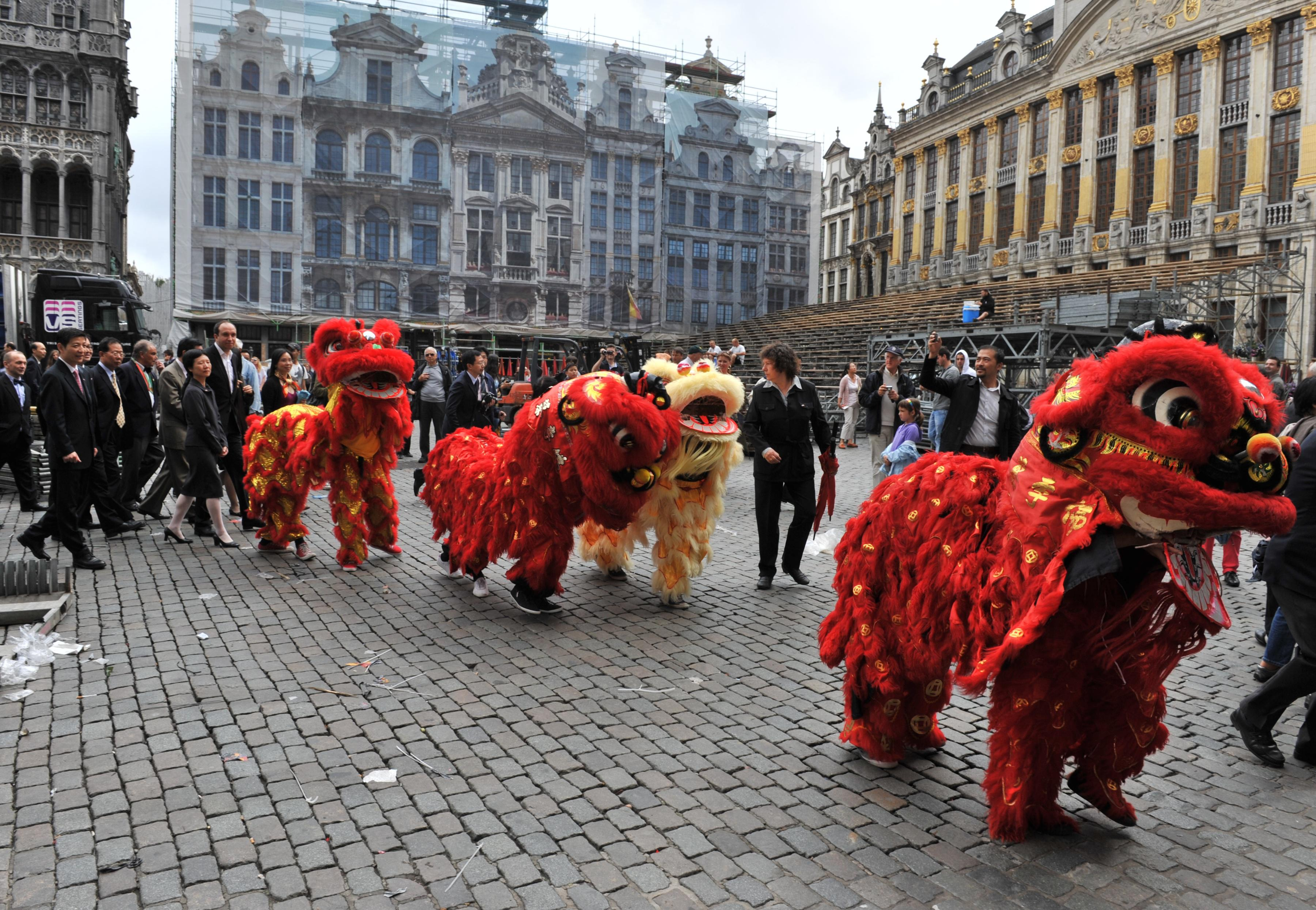 Chinese lions open the way on July 6, 2012, on the Grand Place in Brussels, to Belgian and Chinese personalities, heading to attend a ceremony at the nearby famous Manneken-Pis fountain.