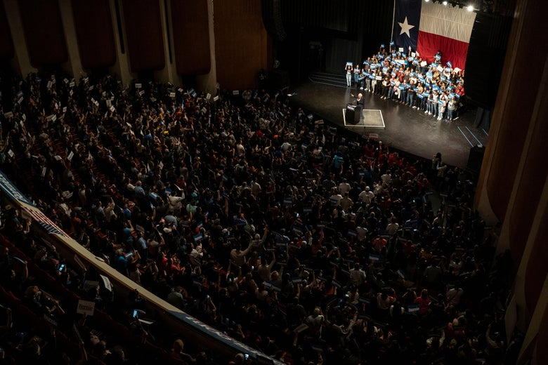 Seen from high up inside a theater, the tiny figure of Bernie Sanders stands on a brightly lit stage with a Texas flag at the back, addressing a full audience.