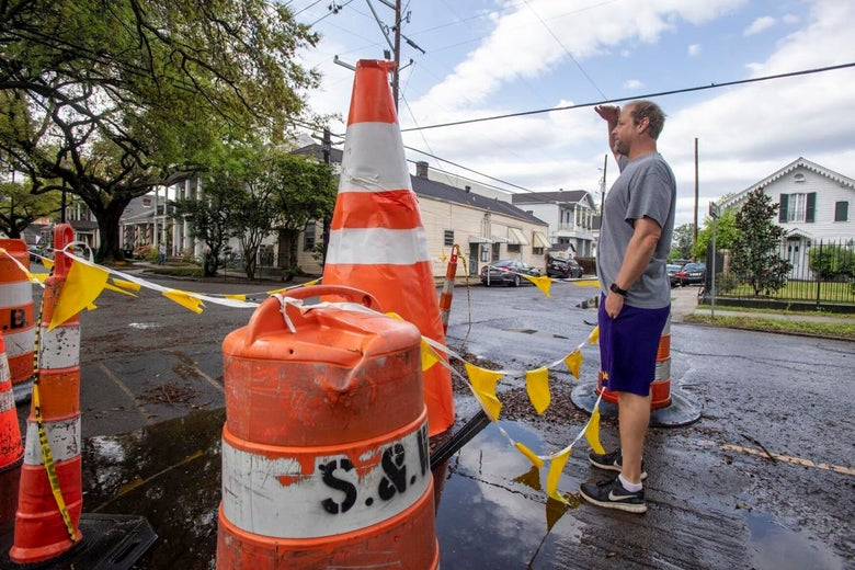 A man holds his hand up to his forehead and stares at an 8-foot-tall orange traffic cone a few feet from him on a New Orleans street.