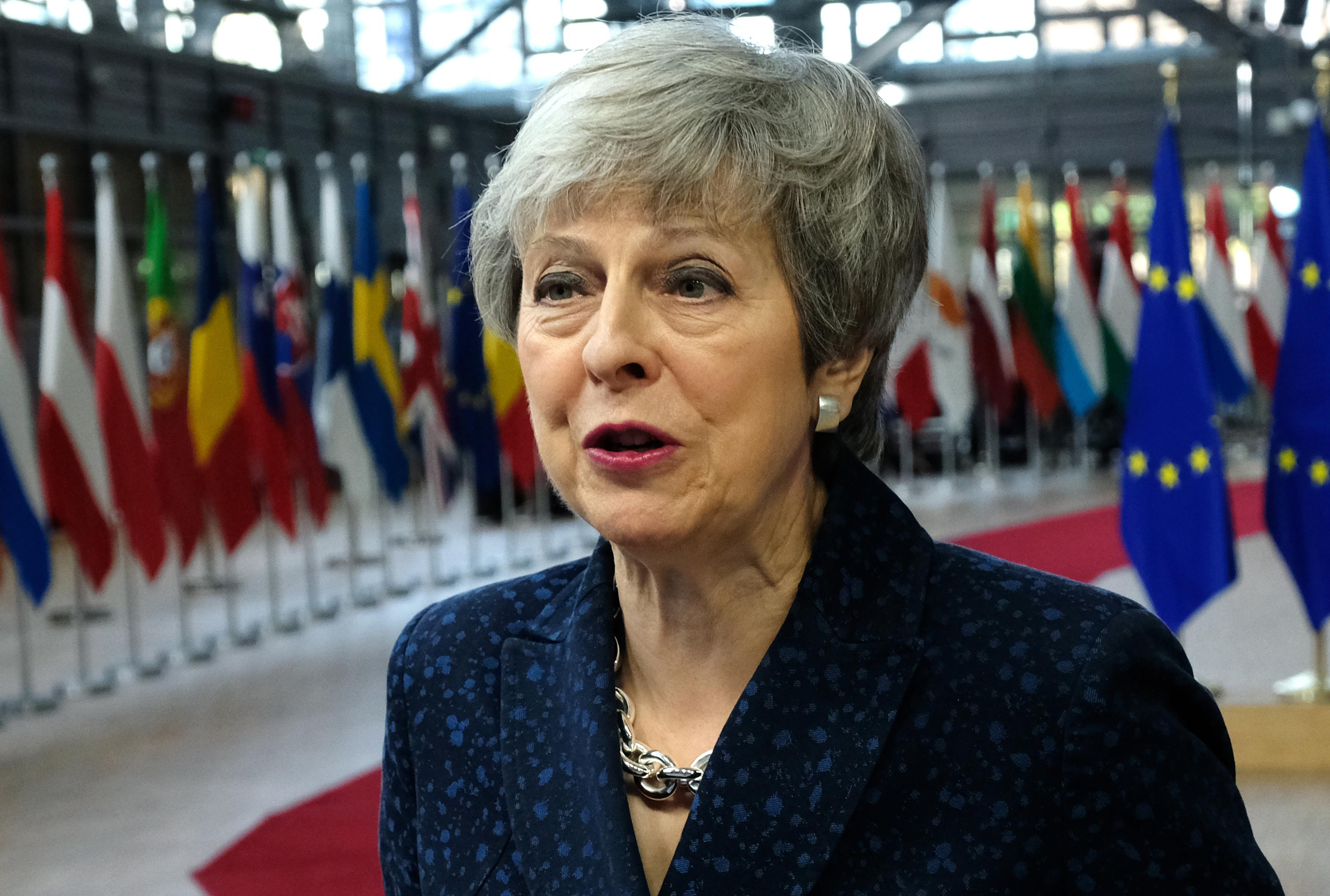 Theresa May in front of flags of various European countries.