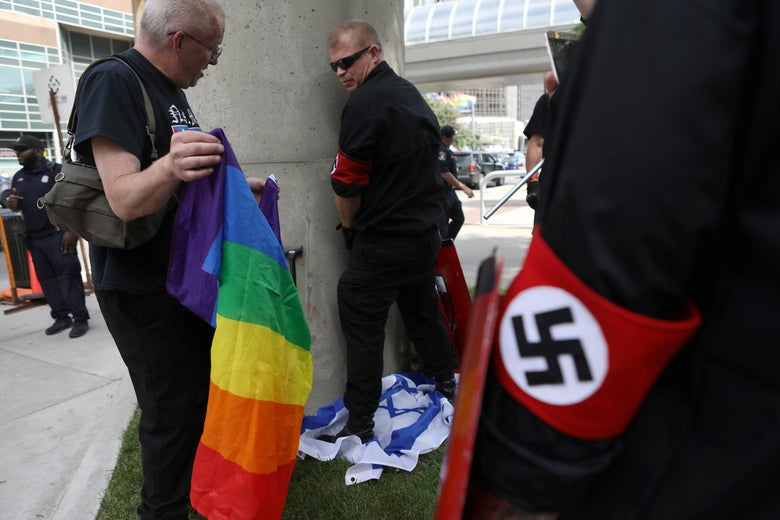 A group of neo-Nazis, one holding a rainbow pride flag, one stepping on an Israeli flag. A law enforcement official stands in the background.
