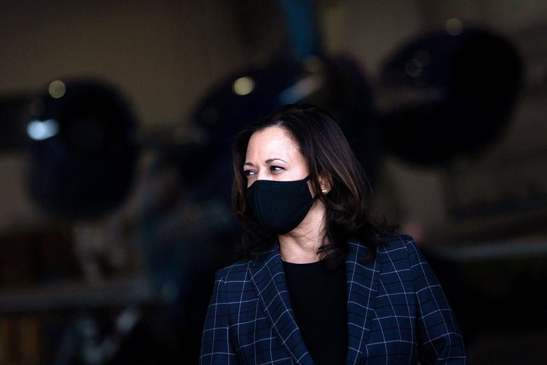 Kamala Harris wearing a face mask with an airplane in the background.