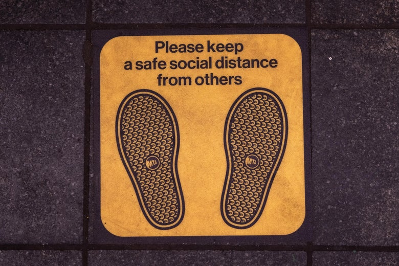 Signage on the floor of the Times Square subway platform asks commuter to maintain a safe social distance.
