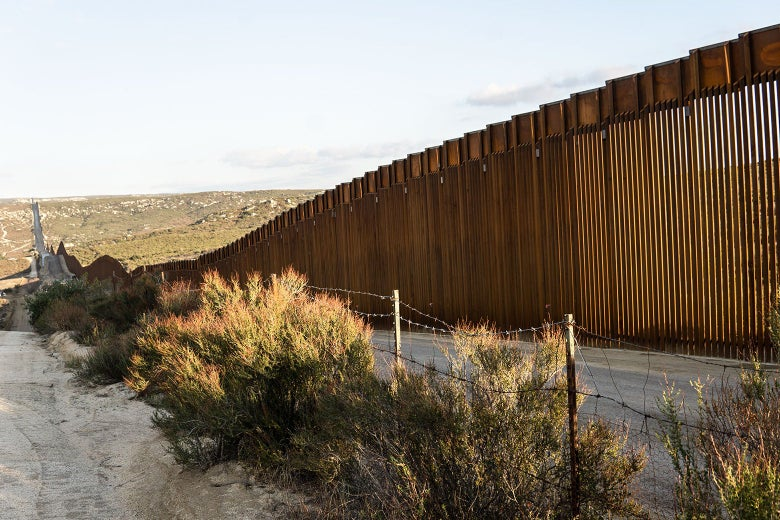 Two bare dirt roadways, separated by a line of bushes and a sagging barbed-wire fence, run alongside the tall, rust-colored shape of the United States border wall, which stands tall on the right side of the picture and recedes into the distance from right to left, diminishing as it traces the undulating landscape.