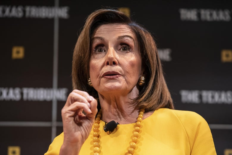 Nancy Pelosi gestures with her hand in front of a Texas Tribune backdrop.