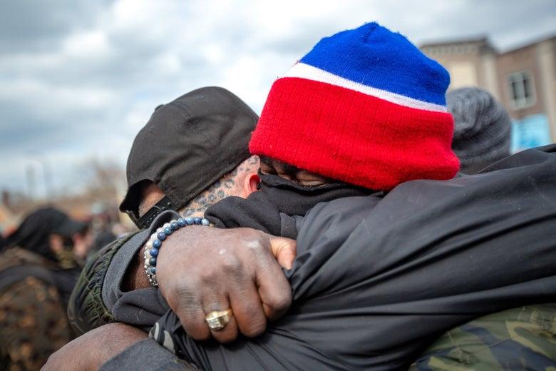 Two men hug in George Floyd Square.