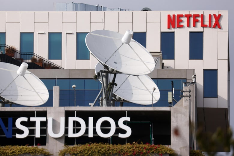 Exterior shot of a building with a Netflix sign in the background and a building with the word Studios on a logo and multiple satellite dishes on the roof in the foreground.