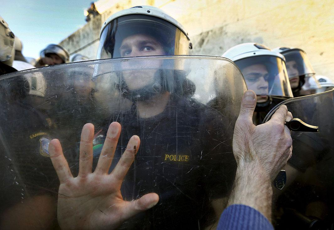 A protester places his hand against the shields of riot policeme