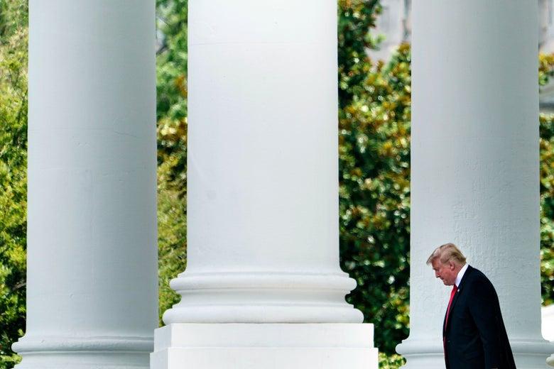 Donald Trump walks by three massive white columns.