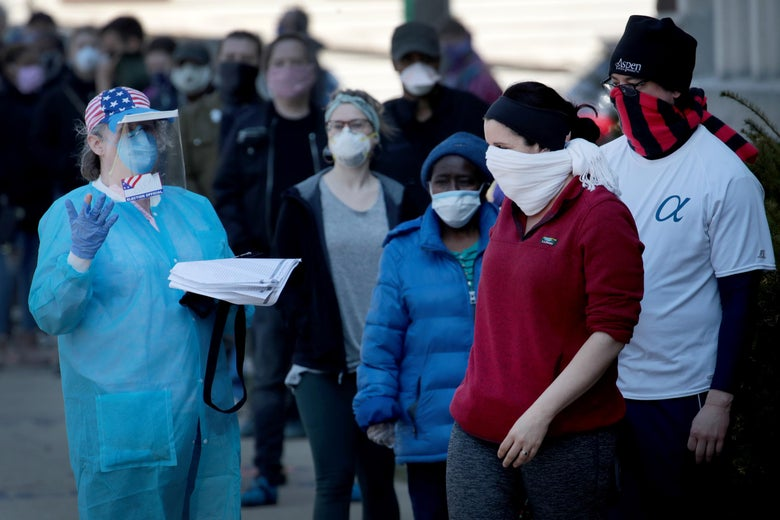 A polling official wearing a gown, gloves, and a face mask directs people who cover their mouths with scarves and masks.