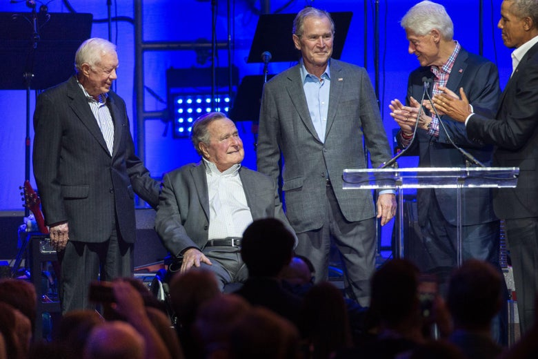 Jimmy Carter looks down toward George H. W. Bush and smiles on his left. To his right, his son George stands and smiles. To his left, Obama and Clinton applaud. They are all standing on a stage set up for a concert.