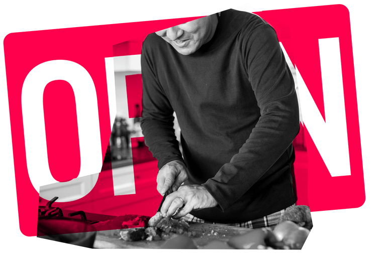 A man in a kitchen, chopping up food. A graphic underneath of an OPEN sign.