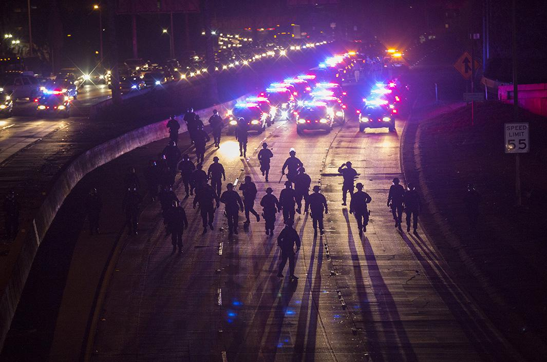 California Highway Patrol officers walk to clear the 101 freeway from protesters in Los Angeles on Nov. 25, 2014