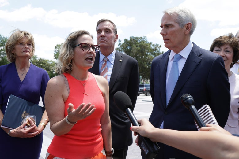 Sinema gestures with one hand as she speaks before a microphone held out by a reporter. Murkowski, Warner, Portman, and Collins stand around her outside.